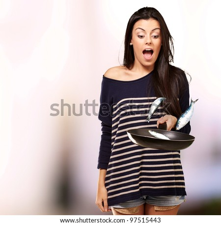 portrait of young girl cooking unruly fishes on pan over abstract background - stock photo