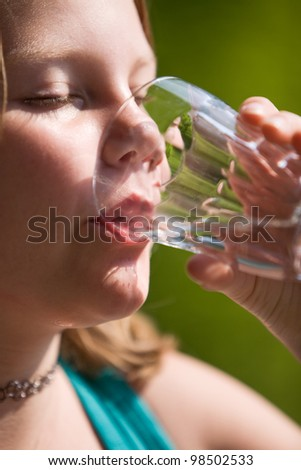 Portrait of young girl drinking mineral water - stock photo