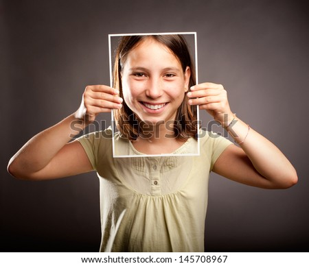 portrait of young girl holding a photography of herself with happy expression - stock photo