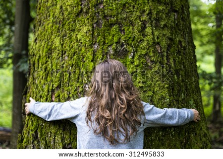 Portrait of young girl hugging a big tree in the forest  - stock photo