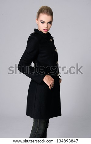 Portrait of young girl in black coat posing over gray - stock photo