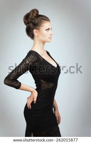 Portrait of young girl in black dress. Portrait of beautiful brunette woman in black dress. Fashion photo - stock photo