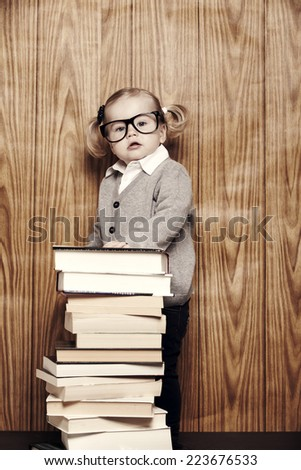 Portrait of young girl in glasses next to books - stock photo