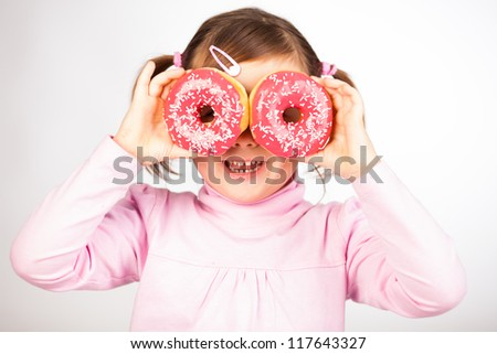 Portrait of young girl looking through two pink donuts, white background, - stock photo