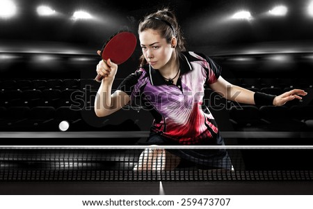 Portrait Of Young Girl Playing Tennis On Black Background with lights - stock photo