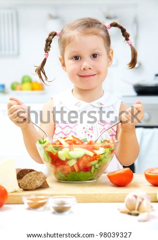 Portrait of young girl preparing healthy food in the kitchen - stock photo