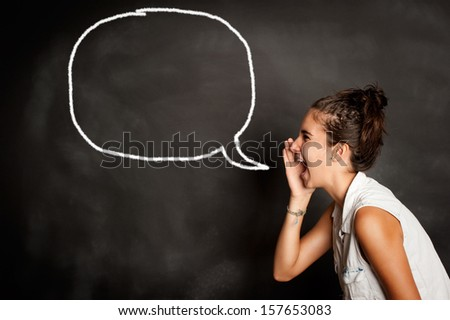 portrait of young girl screaming in front of chalkboard with speech bubble - stock photo