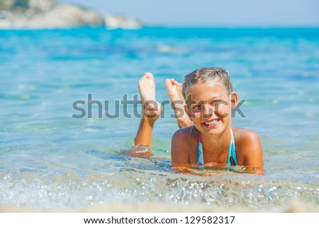 Portrait of young girl swimming in the transparent sea - stock photo
