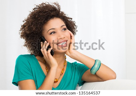 Portrait Of Young Girl Talking On phone Sitting on Couch - stock photo