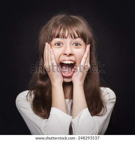Portrait of young girl very emotionally responsive to surprise on a black - stock photo