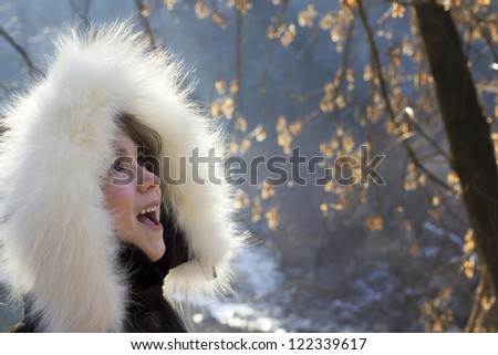 Portrait of young girl wearing fur lined coat hood - stock photo