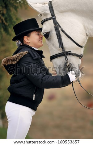 Portrait of young girl with big white horse - stock photo