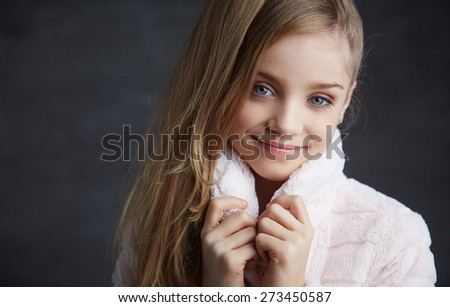 Portrait of young girl with blue eyes in white coat. - stock photo