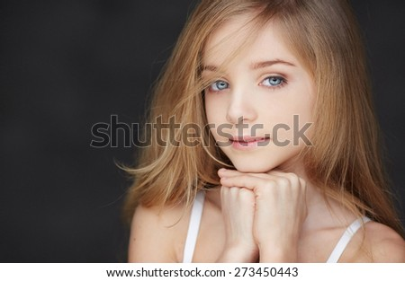 Portrait of young girl with blue eyes on dark background - stock photo