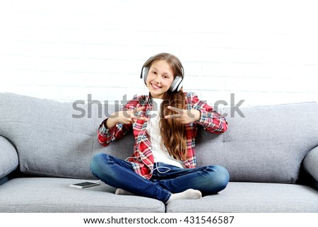 Portrait of young girl with headphones sitting on grey sofa - stock photo
