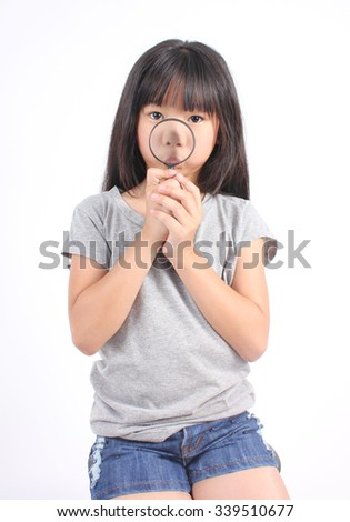 Portrait of young girl with magnifying glass - stock photo