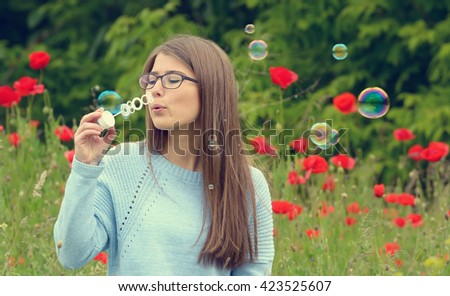 portrait of young girl with soap bubbles in forest - stock photo