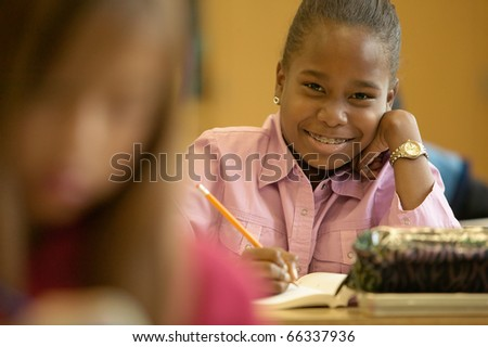 Portrait of young girl working in classroom - stock photo
