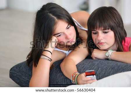 Portrait of young girls laid on a cushion with mobile phone - stock photo