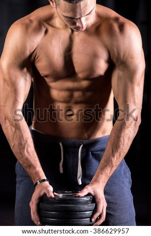 Portrait of young good looking caucasian athletic man working out in gym, leaning on dumbbell, showing strong chest, shoulder and six packs muscles - stock photo