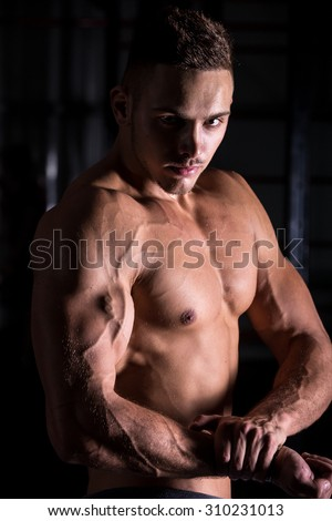 Portrait of young good looking caucasian muscular man working out in gym, posing, showing brawny arms, big biceps, chest muscles, body sculpture concept - stock photo