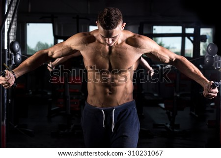 Portrait of young good looking caucasian muscular man working out in sports center, doing chest muscles training on crossover machine in gym, body sculpture concept - stock photo