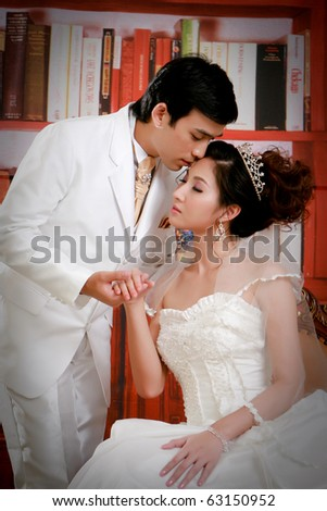Portrait of young groom kissing his bride - stock photo