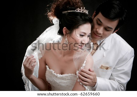 Portrait of young groom looking his bride from backside in erotic emotion at black background - stock photo