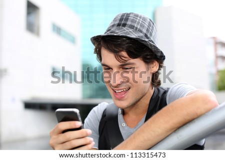 Portrait of young guy sending message with smartphone - stock photo