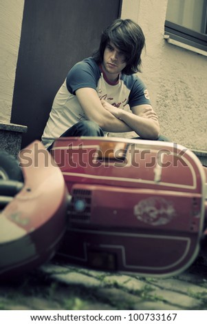 Portrait of young guy with motorbike - stock photo