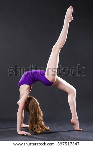 Portrait of young gymnast doing back bend - stock photo
