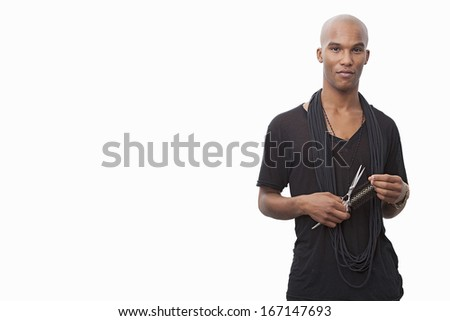 Portrait of young hairstylist standing against white background - stock photo