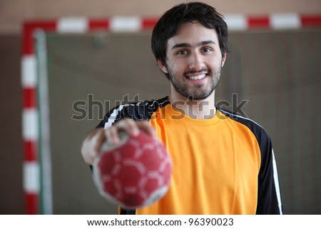 portrait of young handball player holding out ball - stock photo