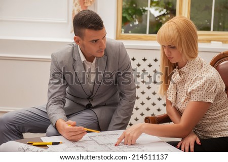 Portrait of young handsome architect discussing ground plan with beautiful blonde woman client sitting at the table in design studio, window on the background - stock photo