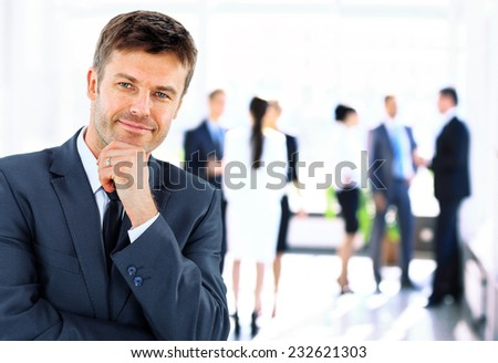 Portrait of young handsome businessman in office with colleagues in the background - stock photo