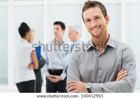 Portrait Of Young Handsome Businessman Smiling In Office - stock photo