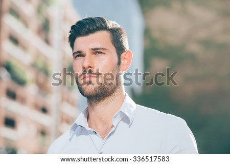 Portrait of young handsome caucasian black hair modern businessman posing in the city backlight, overlooking right - successful, business concept - stock photo