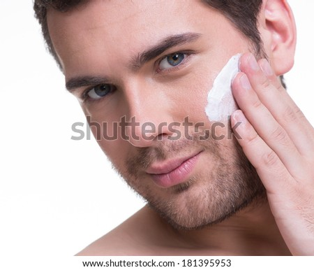 Portrait of young handsome man applying cream lotion on face - isolated on white. - stock photo