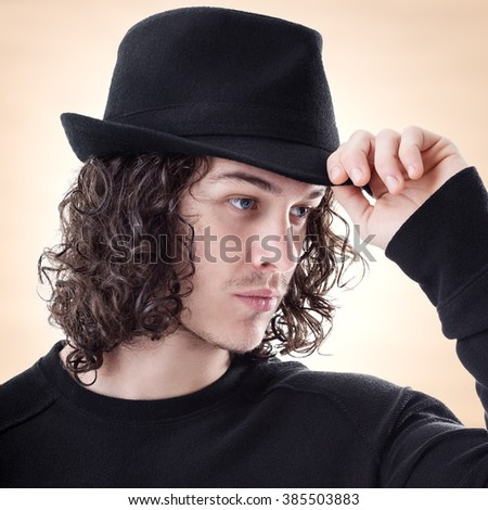 Portrait of young handsome man greet someone with hat - stock photo