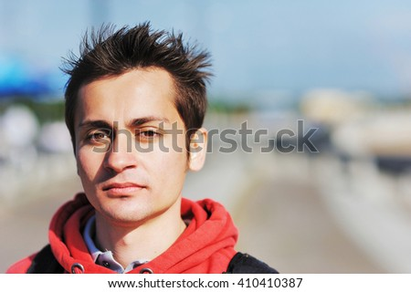 portrait of young handsome man in a red hoodie  - stock photo