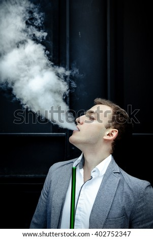 Portrait of Young handsome man in blue suit smoking hookah with weathered brick wall on background - stock photo