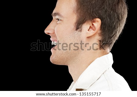 Portrait of young handsome man in profile close up on black background. - stock photo