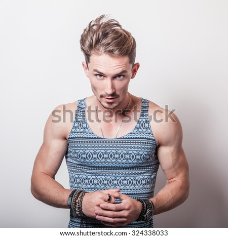 Portrait of young handsome man in turquoise T-shirt with ornament pose in studio.  - stock photo