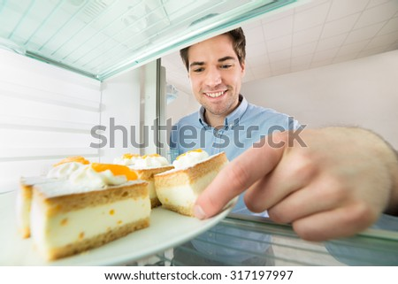Portrait Of Young Handsome Man Taking Cake View From Inside The Refrigerator - stock photo