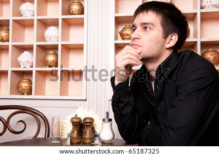 Portrait of young, handsome man thinking and waiting for woman in cafe - stock photo