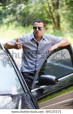 Portrait of young handsome man wearing sunglasses and showing thumbs-up gesture, standing near car. - stock photo