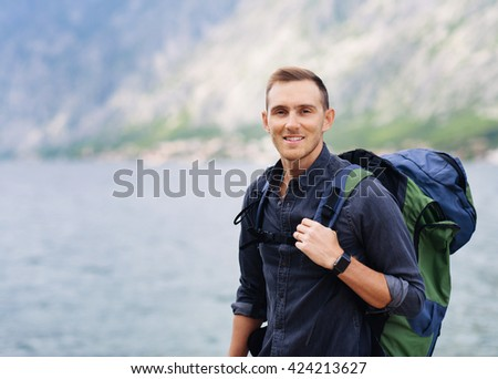 Portrait of young handsome man with backpack outdoor - stock photo