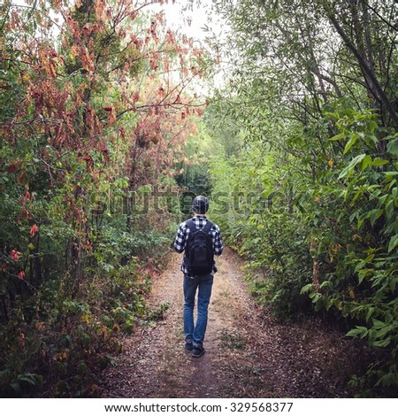 Portrait of young handsome man with backpack wanderer walk in the woods. nature - stock photo
