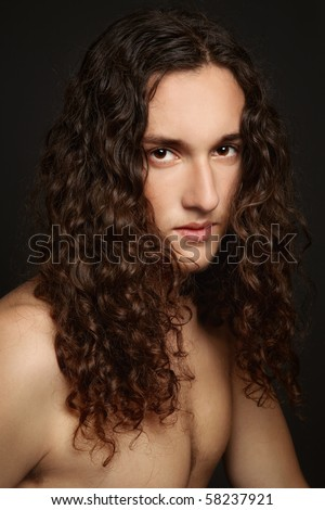Portrait of young handsome man with beautiful long curly hair - stock photo