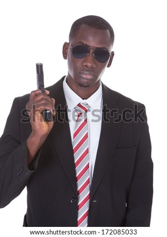 Portrait Of Young Handsome Man With Black Sunglasses And Gun - stock photo